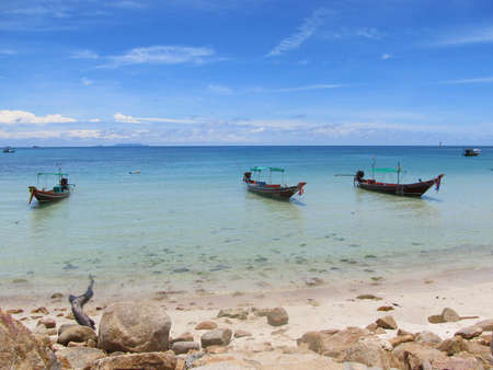 Tropical beach with three boats in Thailand photo
