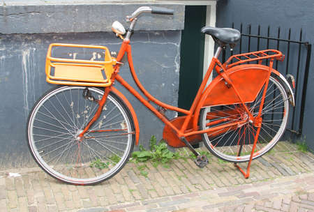 An old orange colored bike in Holland Stock Photo