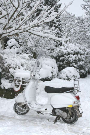 A white scooter parked between a thick layer of snow photo