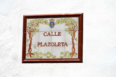 Street sign of old tiles in Andalusia isolated at a white background Stock Photo