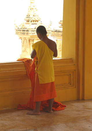 Buddhist monk in orange and yellow robe photo