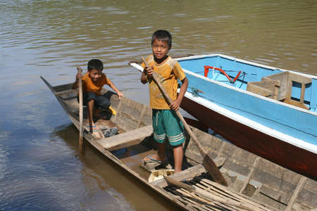 ou: Two boys in a canoe at the Nam Ou river in Laos
