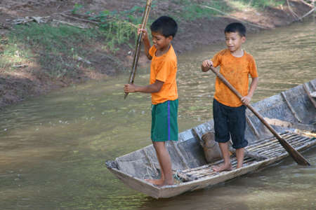 ou: Two boys are canoeing at the Nam Ou river in Laos