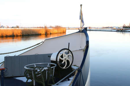 eem: Boat in a frozen river in a Dutch polder Editorial
