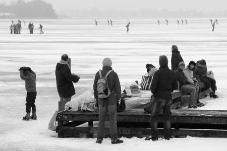 plassen: Skaters on a frozen lake in Loosdrecht in Holland in black and white Editorial
