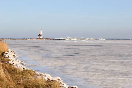 Frozen IJsselmeer and the lighthouse of the village Marken Stock Photo - 17687924