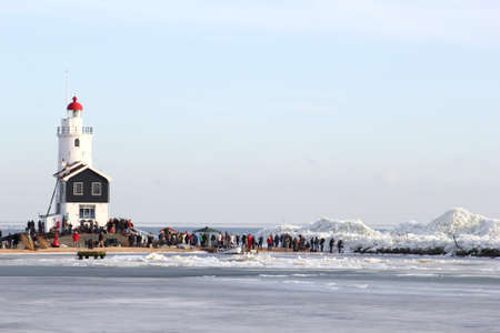 drifting ice: Tourists are watching the drifting ice near the lighthouse of Marken Stock Photo