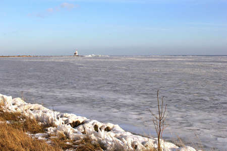 Frozen IJsselmeer with the lighthouse Paard van Marken Stock Photo - 17687940