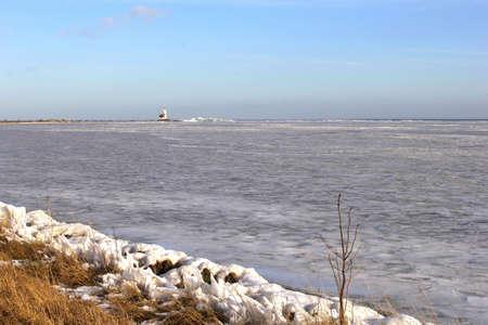 Frozen IJsselmeer with the lighthouse Paard van Marken Stock Photo - 17687940