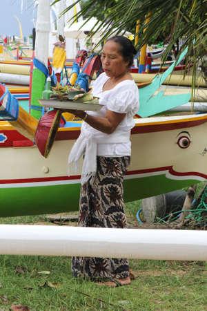 sanur: Balinese woman brings offerings at the beach in Sanur