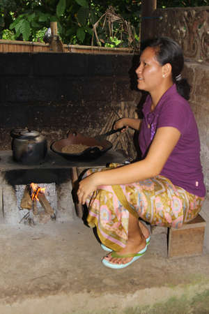Woman is roasting coffee beans from the civets. This is a very tasteful and expensive coffee at Bali