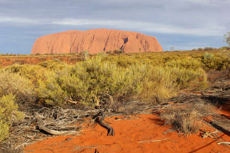 Landscape wit red sand and a view at Uluru