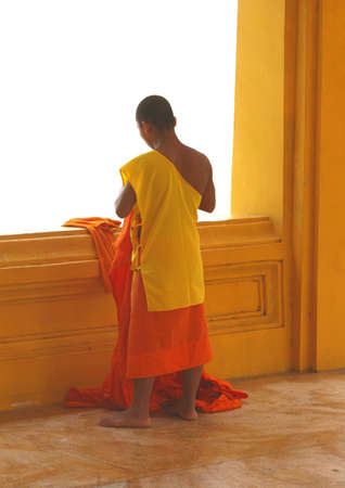 future buddha: Buddhist monk in an orange and yellow rope in a Buddhist temple in Laos Stock Photo