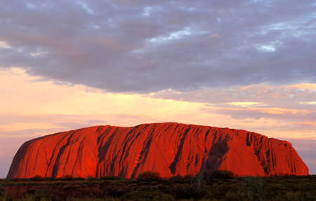 Ayers Rock, Northern Territory, Australia, march 25, 2013 Sunset and a red coloured Uluru nset at Uluru Ayers Rock during a picknick with a glass of wine