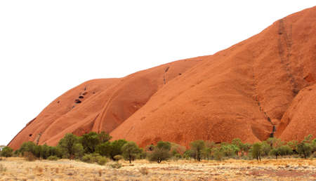 Landscape with green trees and a part of Ayers Rock in the Australian desert