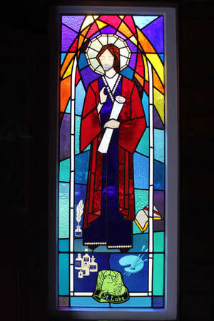April 17, 2013 Stained glass window with Saint Luke isolated on a black background