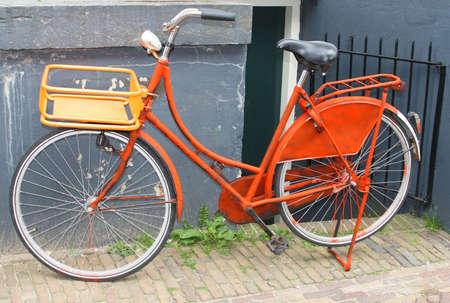 Vintage orange bike against a grunge wall in Amsterdam