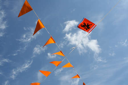 Dutch orange flags and the Dutch lion against a blue sky in the Netherlands photo