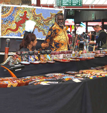 Melbourne, Victoria, Australia, april 2, 2013 An Aboriginal man sells Aboriginal art at the historical Queen Victoria Market in Melbourne. This market is operating since 1878