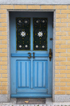 A vintage blue wooden door is decorated with white flowers