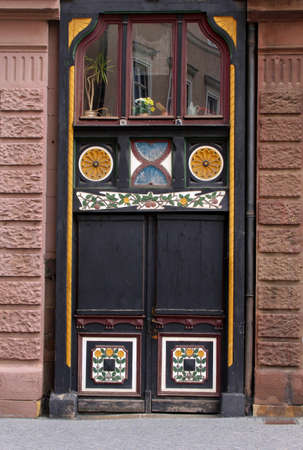 A medieval vintage brown wooden door is decorated with yellow and white ornaments photo
