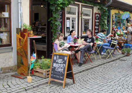 Erfurt, Thuringen, Germany, august 7, 2013 Tourists are relaxing at a terrace on the medieval Merchants Bridge Kraemerbruecke in the historical city centre of Erfurt in Thuringia Germany