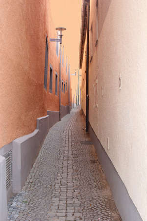 Narrow street with cobblestone and salmon colored walls in eastern Europe photo