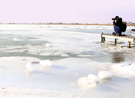 Marken, Netherlands, januari 28, 2013 A photographer enjoys the frozen big lake IJsselmeer near Amsterdam