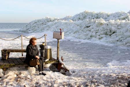 ijsselmeer: Marken, Netherlands, januari 28, 2013 A woman enjoys the drifting ice in the big lake IJsselmeer near Amsterdam  Editorial