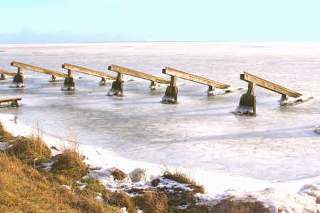 Jetties in a frozen lake Markermeer near the village Marken in the Netherlands photo