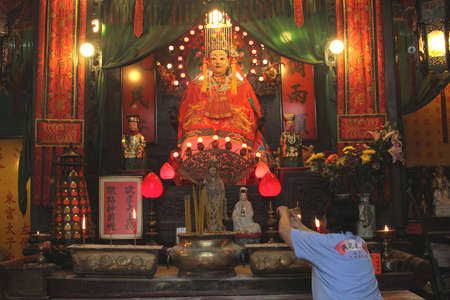 worshipping: Hong Kong, Kowloon, China, 6 november, 2013 A woman is worshipping the goddess of the sea in the Tin Hau temple which was built in 1767 and is now the oldest building in Hong Kong