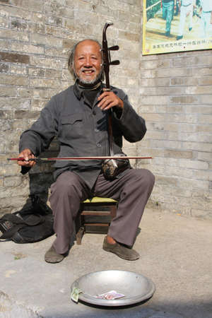 Xingping, province Guangdong, China, november 20, 2013  A man is playing the traditional musical instrument which is called Erhu or Nanhu and looks like a violin