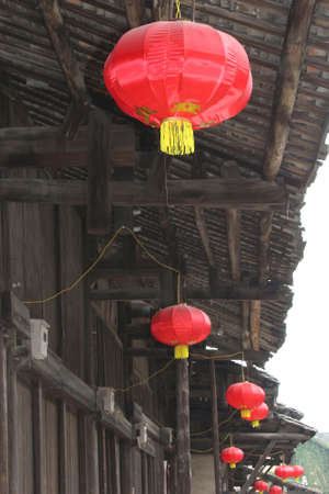 richness: Red lanterns at old wooden houses in an old traditional Chinese village; red lantern means prosperity, richness and happiness