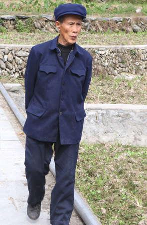 Longji, Guangxi, China, november 19, 2013 Elderly man in traditional blue Mao suit is walking along the rice terraces