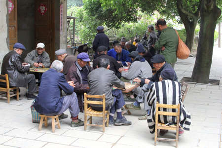 Daxu, province Guangxi, China, november 21, 2013 Man in traditional blue Mao suits are playing cards in the old village Daxu near Guilin