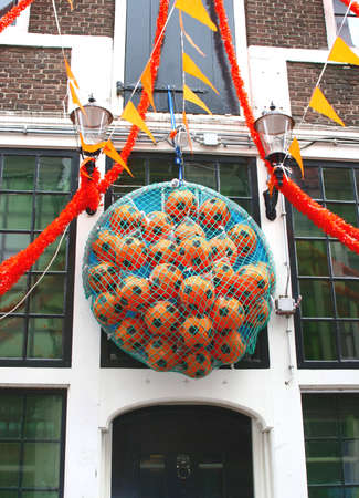 folkloristic: Orange decorations and footballs for WK 2014 along a canal house in Amsterdam, Netherlands Stock Photo
