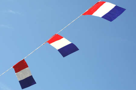 Dutch national flags against a blue sky