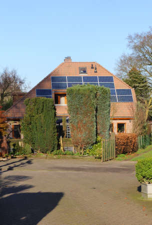 durable: Traditional old house with modern solar panels at the roof