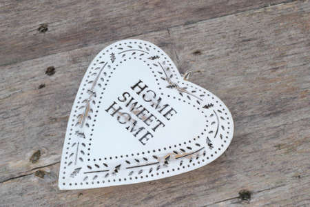 Heart with text Home Sweet Home, isolated at a weathered wooden background  photo