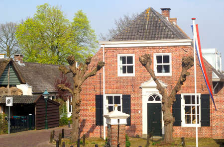 typically dutch: April 2014 Characteristic ancient Dutch house with the Dutch national flag