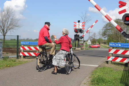 April 2014 Elderly couple on bikes waits at the railway crossing, Netherlands