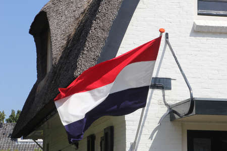 National flag of the Kingdom of the Netherlands at the facade of a house