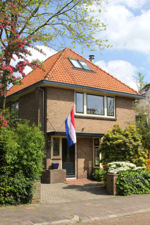 soest: Soest, Netherlands, april 2014 Dutch villa with garden and the national Dutch flag  Editorial