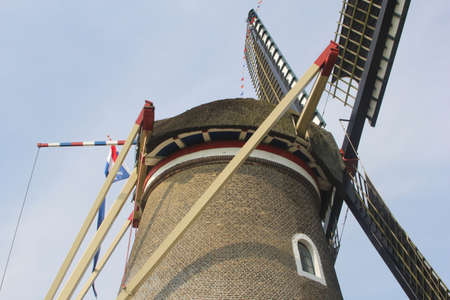 Structures of a traditional corn windmill - called the Freedom - with Dutch flags, Holland photo