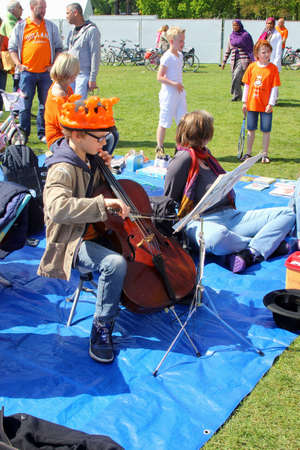 making music: Holland, april 2014 Boy with orange crown is making music at a violin at Kingsday