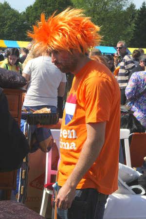folkloristic: Holland, april 2014 Man with orange shirt and orange hair   Editorial