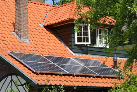 electrics: Modern solar panels at a roof with red tiles
