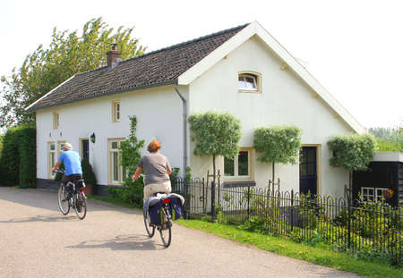 typically dutch: Tricht, Betuwe, Netherlands, april 2014 Cycling along a traditional Dutch house in the Betuwe  Editorial