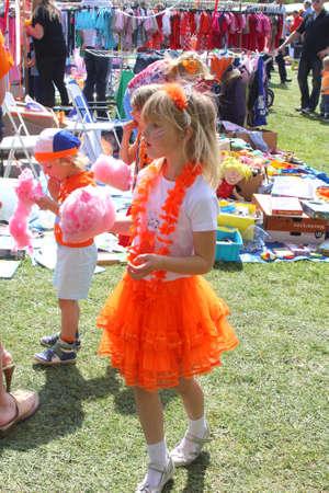 folkloristic: Netherlands, april 2014 Dutch girl with orange princess dress enjoys cotton candy Editorial