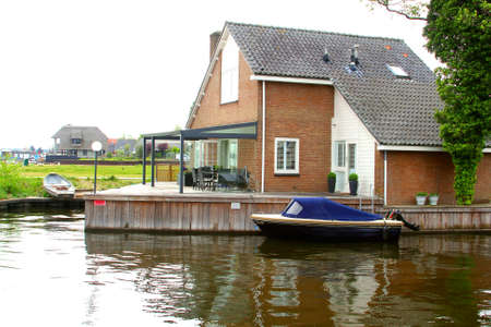 plassen: Loosdrecht, Holland, may 2014 Modern detached house with a boat and terrace  along the lakes of Loosdrecht